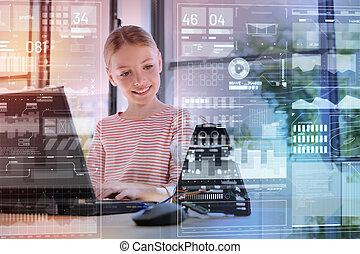 Smiling girl looking at the robot and putting her fingers on keyboard