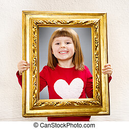 smiling girl looking through a vintage picture frame