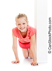 Smiling girl looks out from behind a white wall