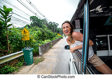 smiling girl looks out of the window of a taxi, tuk-Tuk