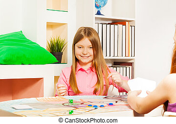 Smiling girl making her move at the gaming table