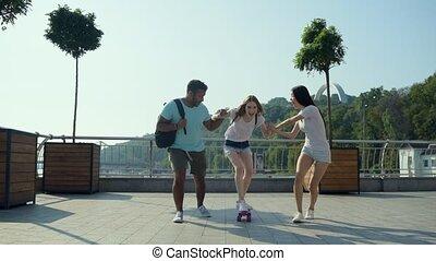 Smiling girl mastering skateboarding skills outdoors