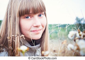 smiling girl on a meadow in autumn