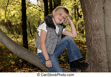 smiling girl on autumn tree branch