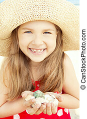 smiling girl on beach hold shells