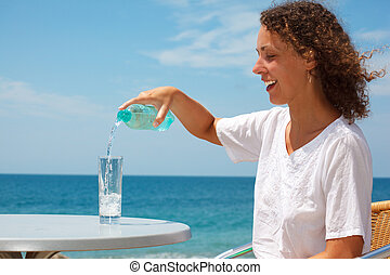 Smiling girl on beach. One sunny summer day sitting at table and pours water into glass.