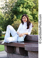 Smiling girl on stone bench