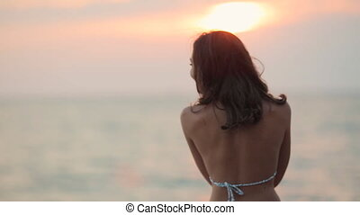 Smiling girl on sunset standing in the sea