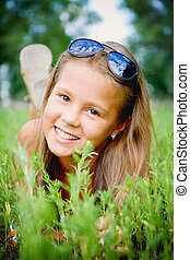 Smiling girl on the grass.