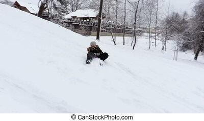 Smiling girl on toboggan in snow
