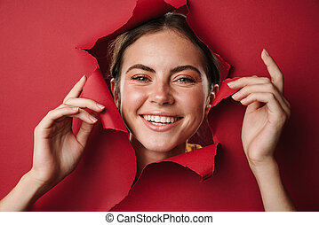 Smiling girl peeping through hole in paper