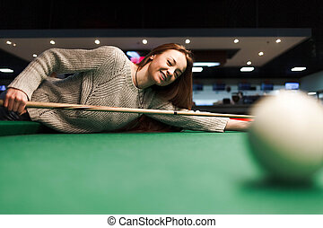Smiling girl plays billiards in the club