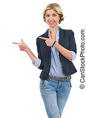 Smiling girl pointing on copy space