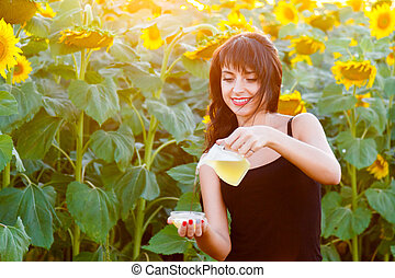 Smiling girl pours sunflower oil from a jug into a bowl