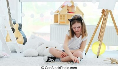Smiling little girl putting on lips and glasses on sticks sitting in playroom