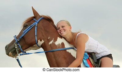 Smiling girl rider in saddle embracing her horse