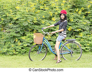 Smiling girl riding a bicycle in the park