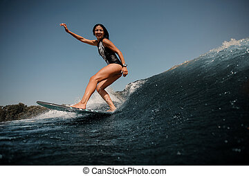 Smiling girl riding on the wakeboard on the lake