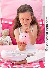 Smiling girl saving money in a piggybank
