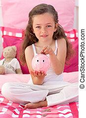 Smiling girl saving money in a piggybank on bed