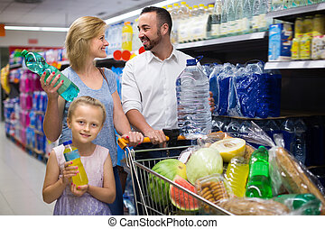 Smiling girl selecting non-alcoholic beverage in plastic bottle in food store