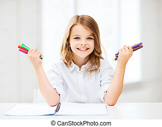 smiling girl showing colorful felt-tip pens - education,...