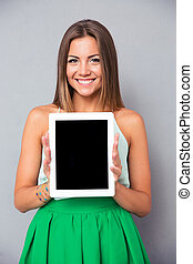 Smiling girl showing tablet computer screen over gray ...