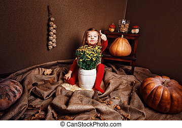 Smiling girl showing thumb up sitting with vase of flowers