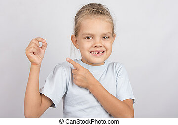 Smiling girl shows a finger on a fallen baby tooth