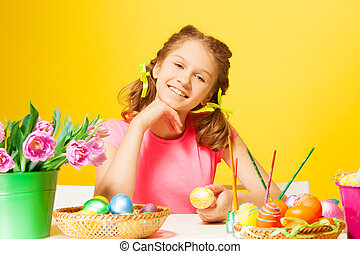 Smiling girl sits at the table with Easter eggs