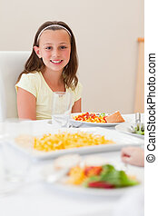 Smiling girl sitting at dinner table