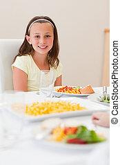 Smiling girl sitting at dinner table
