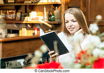 smiling girl sitting at summer terrace and reading book