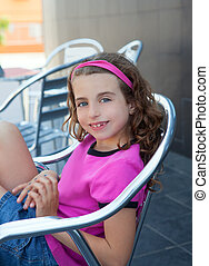 Smiling girl sitting in outdoor aluminium chair