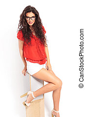 smiling girl sitting in studio on a chair with her leg up