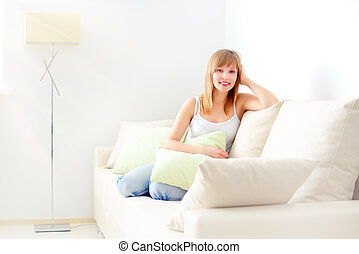 smiling girl sitting on sofa