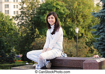 Smiling girl sitting on stone bench