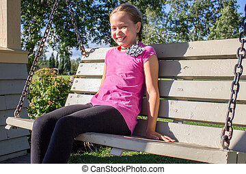 Smiling girl sitting on swing bench in the park