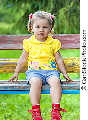 Smiling girl sitting on the bench