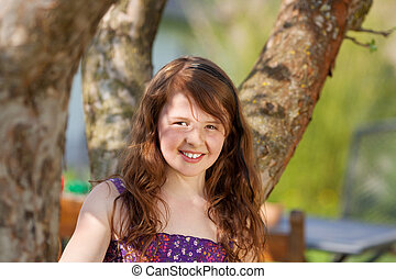 smiling girl sitting under a tree