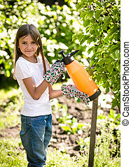 smiling girl spraying small apple tree with fertilizers