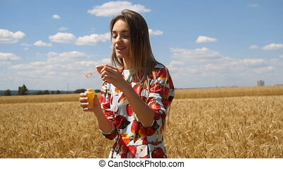 smiling girl standing in a wheat field and inflates soap-bubbles