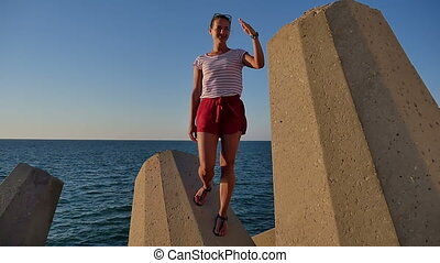 Smiling girl standing on blocks and saluting in a funny way