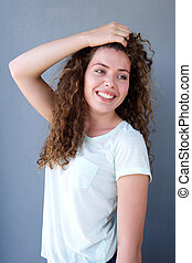 Smiling girl standing with hand in hair
