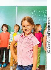 Smiling girl stands near green blackboard
