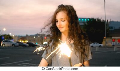 Smiling girl start sparkler by match in night street with out of focus city lights on background.