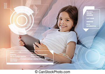 Smiling girl staying in hospital bed and holding a modern tablet