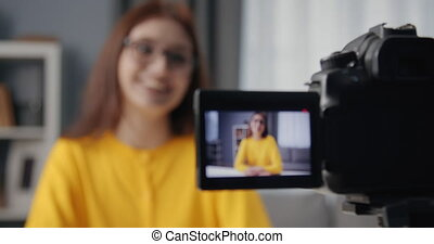 Smiling girl talking on camera while shooting new video - ...