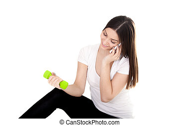 Smiling girl talking on phone and lifting dumbbells