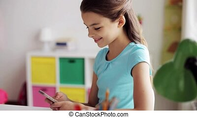 smiling girl texting on smartphone at home - people,...